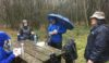"The ""hill"" looms behind the picnickers in the rain"